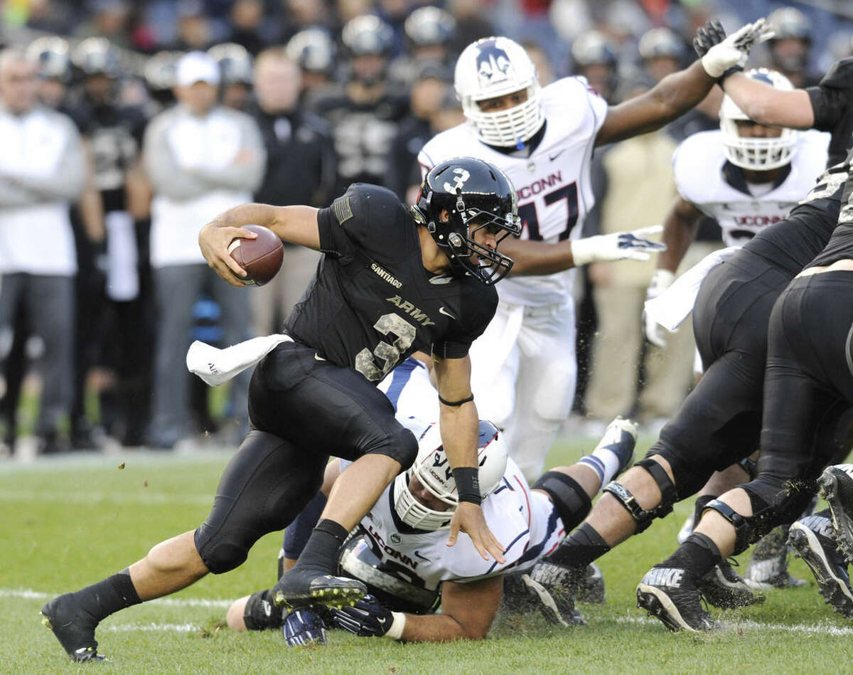 Army quarterback Angel Santiago (3) runs with the ball during the first half of a college football game against Connecticut Saturday, Nov. 8, 2014, at Yankee Stadium in New York. (AP Photo/Bill Kostroun)