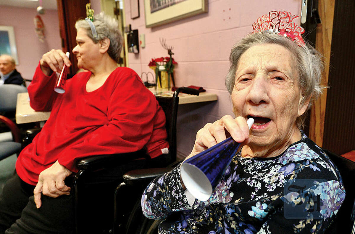 Hour photo / Erik Trautmann Notre Dame Convalescent Home residents including Pauline Fuscoe, right, take part in the facility's New Year's celebration Thursday afternoon.