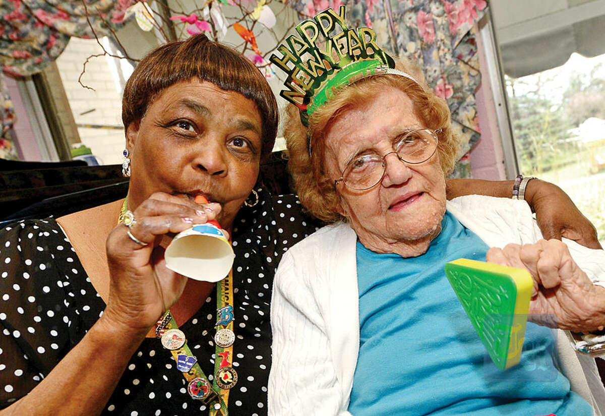 Hour photo / Erik Trautmann Notre Dame Convalescent Home resident Elizabeth Vareha and staffer Kethrine Hinds take part in the facility's New Year's celebration Thursday afternoon.