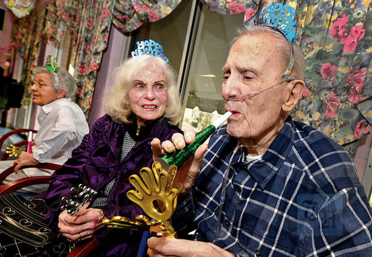 Hour photo / Erik Trautmann Notre Dame Convalescent Home resident John Anderson and his guest, Evelyn Varga, take part in the facility's New Year's celebration Thursday afternoon.