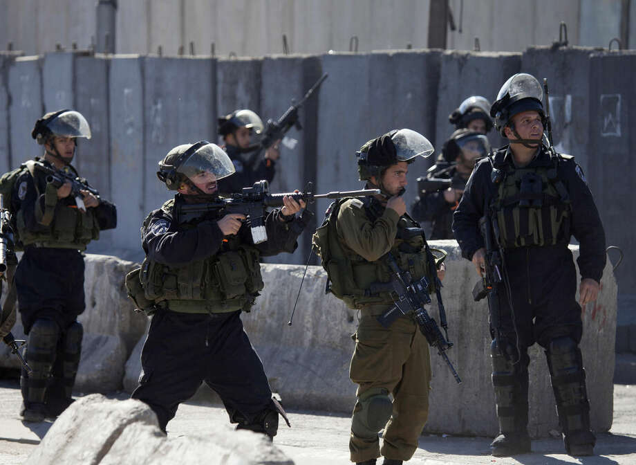 An Israeli border policeman aims his weapon during clashes with Palestinians following a protest against Israeli restrictions to Al-Aqsa Mosque in Jerusalem, at Qalandia checkpoint near the West Bank city of Ramallah, Friday, Nov. 7, 2014. (AP Photo/Majdi Mohammed)