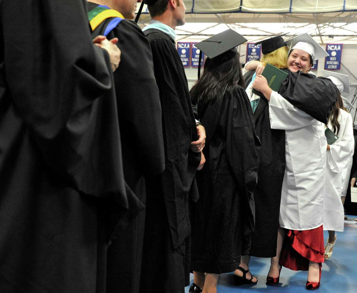 Hannah Grace Brust gets a hug from a faculty members after receiving her degree during the New Milford High School 2016 Graduation Exercise, on June 11, 2016, at the O'Neill Center, Western Connecticut State University, Danbury, Conn.