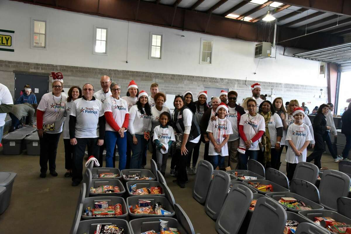 Patriot employees volunteer to fill food bins for Al's Angels Holiday Meal Assembly. Each bin contains more than $100 worth of non-perishable food items that will feed a family of four.