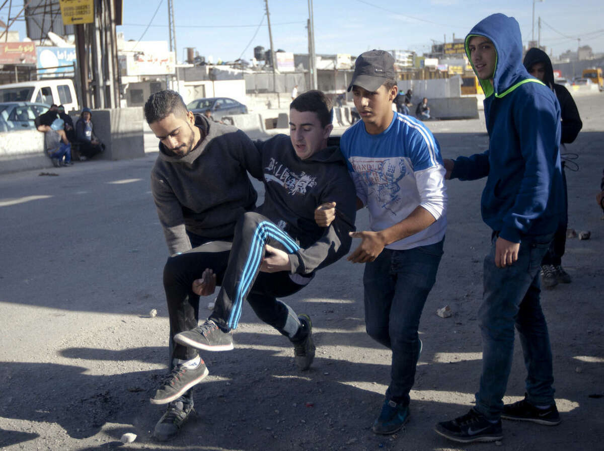 Palestinians carry an injured man during clashes with Israeli forces following a protest against Israeli restrictions to Al-Aqsa Mosque in Jerusalem, at Qalandia checkpoint near the West Bank city of Ramallah, Friday, Nov. 7, 2014. (AP Photo/Majdi Mohammed)
