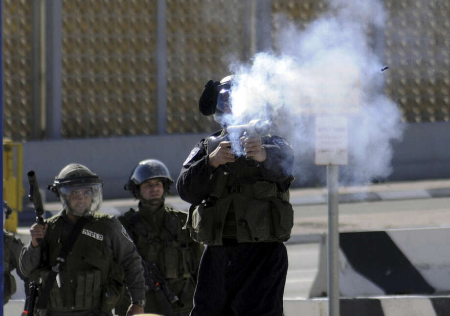 An Israeli border policeman shoots a rubber-coated bullet during clashes with Palestinians, as Israeli police limited the access to Al-Aqsa Mosque in Jerusalem on Friday, Nov. 7, 2014. Tensions have been rising in recent weeks over the Jerusalem shrine, known to Muslims as Haram al-Sharif, or Noble Sanctuary, and to Jews as the Temple Mount. (AP Photo/Mahmoud Illean)