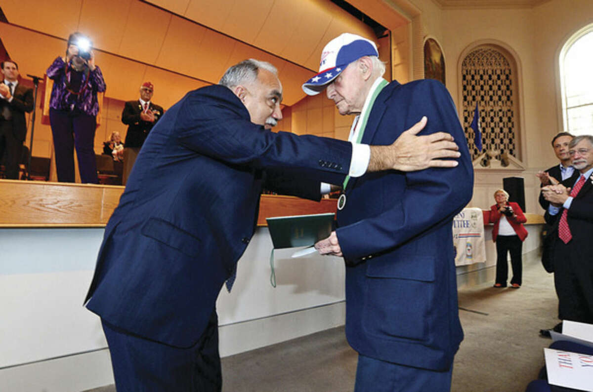 Hour photo/Erik Trautmann Norwalk Superintendent of Schools Manual Rivera presents WWll Army veteran Michael James Hegedus with a honorary diploma during the Norwalk Veterans Day celebration at Ciy Hall Tuesday morning.