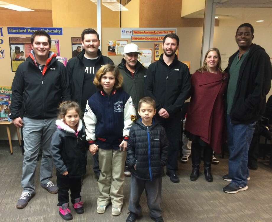 "From left, back row: Ben Wetmore, Levi Flaherty, and Sam Herman, from New Country MINI were greeted by Hartford Public School Superintendent Dr. Beth Schiavino-Narvaez and staff when they delivered more than 100 coats collected through New Country's 2nd Annual ""Stuff a MINI to the Max"" campaign.  Happy Hartford students model their new coats."