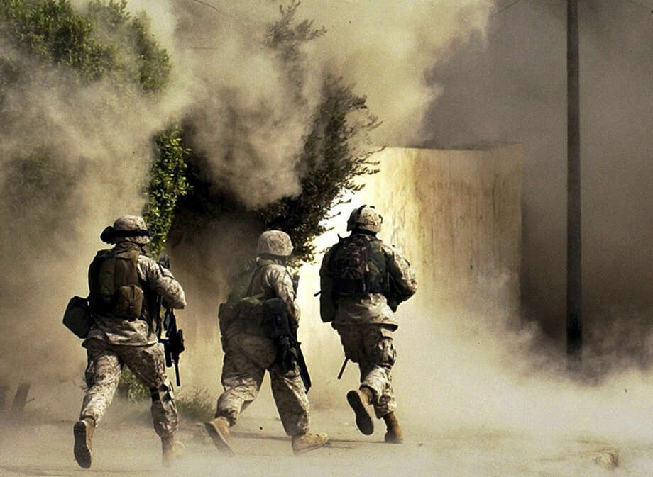 FILE - In this Oct. 26, 2004 file photo, U.S. Marines from the 2nd Battalion, 5th Marine Regiment, run to a building after detonating explosives to open a gate during a mission in Ramadi in Anbar province, Iraq. U.S. President Barack Obama said Friday, Nov. 7, 2014, that he authorized the deployment of up to 1,500 more American troops to bolster Iraqi forces. For the first time since the U.S. withdrawal in December 2011, American military personnel will be on the ground in Iraq's historically dangerous Anbar province, helping train the Iraqi military for its fight against the Islamic State group. Anbar resonates with many Americans because they recall how costly the fighting was there for U.S. troops. More than 3,500 U.S. soldiers died in combat in Iraq between 2003 and 2011 - and there are concerns that sending Americans back to Anbar in any capacity will inevitably make them a target. (AP Photo/Jim MacMillan, File)