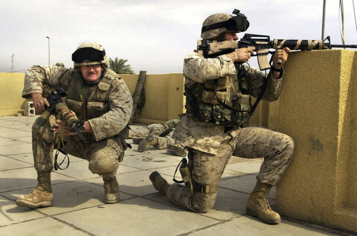 FILE - In this Sunday, Oct. 31, 2004 file photo, U.S. Marine snipers from the 2nd Battalion, 5th Marine Regiment, take cover during a gun battle with insurgents in Ramadi in Anbar province, Iraq. U.S. President Barack Obama said Friday, Nov. 7, 2014, that he authorized the deployment of up to 1,500 more American troops to bolster Iraqi forces. For the first time since the U.S. withdrawal in December 2011, American military personnel will be on the ground in Iraq's historically dangerous Anbar province, helping train the Iraqi military for its fight against the Islamic State group. Anbar resonates with many Americans because they recall how costly the fighting was there for U.S. troops. More than 3,500 U.S. soldiers died in combat in Iraq between 2003 and 2011 - and there are concerns that sending Americans back to Anbar in any capacity will inevitably make them a target. (AP Photo/Jim MacMillan, File)