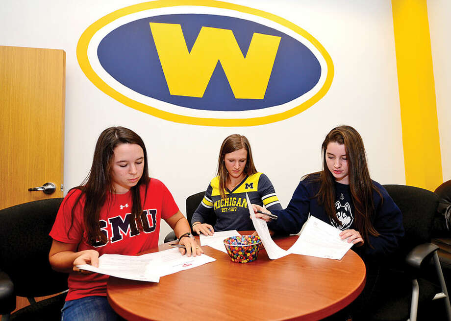 Hour photo / Erik Trautmann Weston High seniors Megan Grotto, Katie Grotto and Bridget Murphy sign their National Letters of Intent Wednesday to row at Division1 colleges, Southern Methodist, Michigan and UCONN respectively.