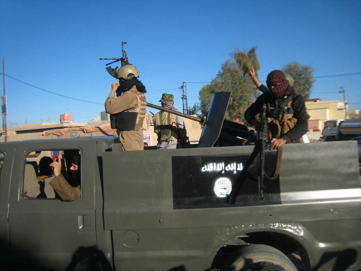 FILE - in this Thursday, March 20, 2014 file photo, Islamic State group militants patrol in a commandeered Iraqi security forces trucks sprayed with the representation of the al-Qaida flag and the Arabic that reads,