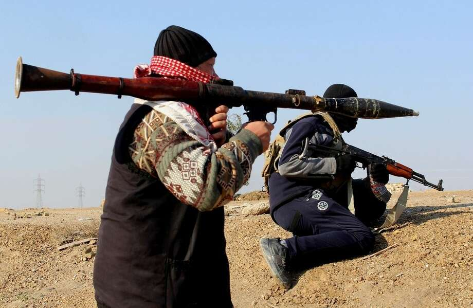 FILE - in this Wednesday, Feb. 12, 2014 file photo, Islamic State group militants hold their weapons in their combat positions in Fallujah, 40 miles (65 kilometers) west of Baghdad, Iraq. U.S. President Barack Obama said Friday, Nov. 7, that he has authorized the deployment of up to 1,500 more American troops to bolster Iraqi forces, which could more than double the total number of U.S. forces to 3,100. For the first time since the U.S. withdrawal in December 2011, American military personnel will be on the ground in Iraq's historically dangerous Anbar province, helping train the Iraqi military for its fight against the Islamic State group. (AP Photo, File)
