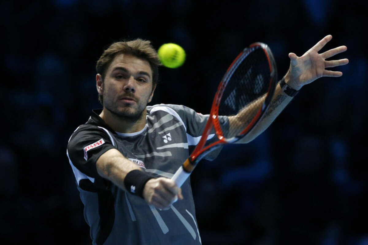Switzerland's Stanislas Wawrinka plays a return to Czech Republic's Tomas Berdych during their singles ATP World Tour tennis finals match at the O2 arena in London, Monday, Nov. 10, 2014. (AP Photo/Alastair Grant)