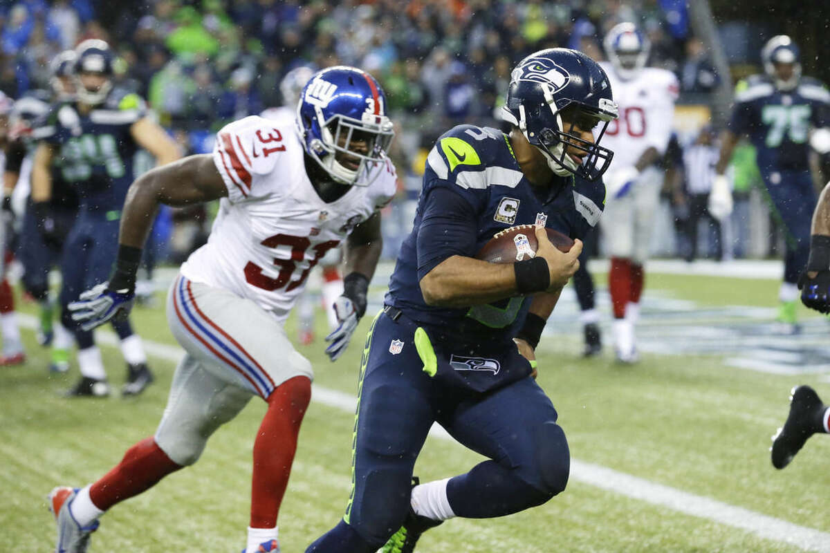 Seattle Seahawks quarterback Russell Wilson, right, runs for a touchdown as New York Giants' Zack Bowman, left, pursues in the second half of an NFL football game, Sunday, Nov. 9, 2014, in Seattle. (AP Photo/Elaine Thompson)