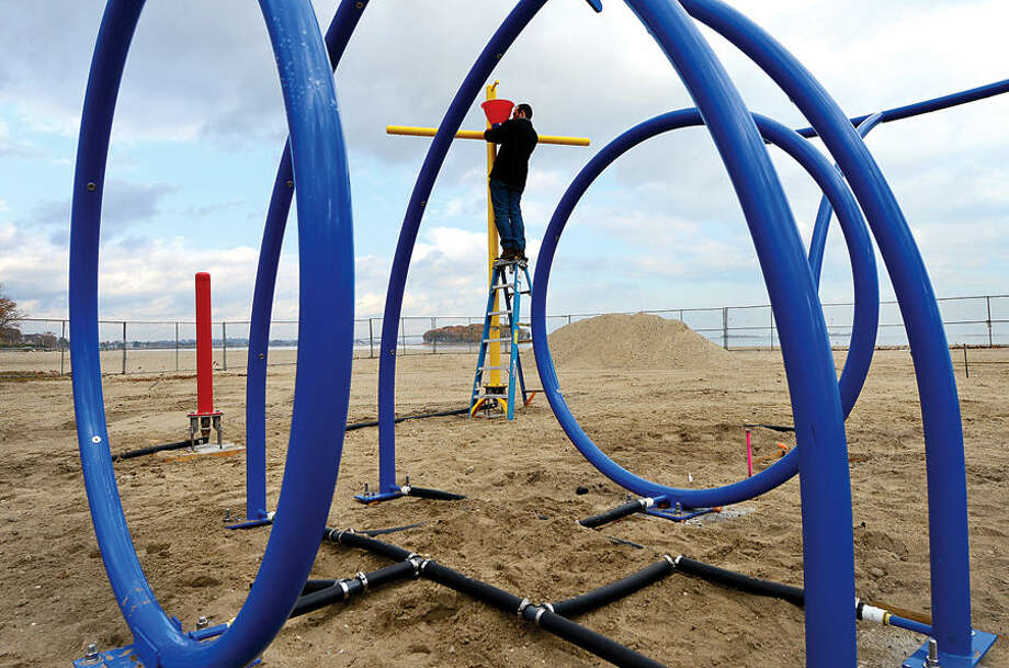 Hour photo / Erik Trautmann Probuilt employee Antonio Vasconcelos puts together the new splash pad at Calf Pasture Beach Wednesday. The water feature is one of many new improvements at Norwalk's main beach.