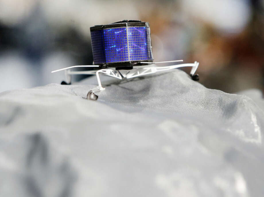 A model of Rosetta lander Philae stands on a model of comet 67P/Churyumov-Gerasimenko, at the European Space Agency ESA in Darmstadt, Germany, Wednesday, Nov.12, 2014. Europe's Rosetta space probe was launched in 2004 with the aim of studying the comet and learning more about one of the biggest questions about the origin of the universe. (AP Photo/Michael Probst)