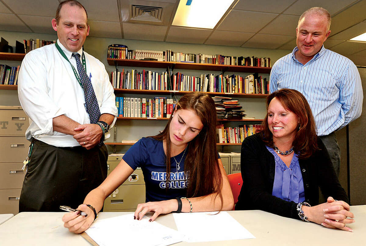 Hour photo / Erik Trautmann Norwalk High Schoolfield hockey player Sam Bartush signs a National Letter of Intent to play at Merrimack College while flanked by coach Kyle Seaburg, mom Eva Bartush and Athletic Director Mark Marchetti.