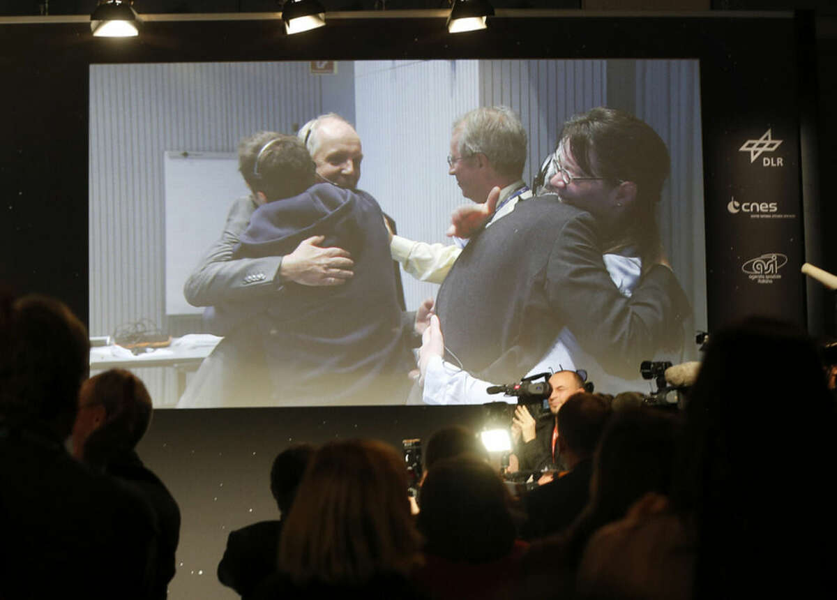Celebrating scientists in the main control room appear on a video screen at the European Space Agency after the first unmanned spacecraft Philae landed on a comet called 67P/Churyumov-Gerasimenko, in Darmstadt, Germany, Wednesday, Nov. 12, 2014. Europe's Rosetta space probe was launched in 2004 with the aim of studying the comet and learning more about the origins of the universe. (AP Photo/Michael Probst)