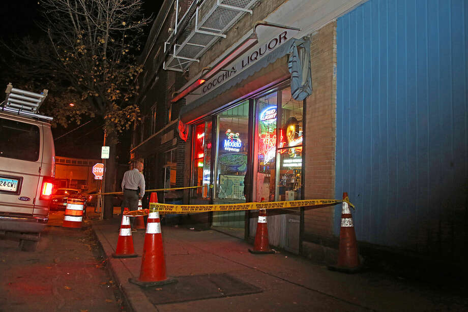 A detective checks out the scene of a stabbing at Cocchia Liquor on Ely Avenue Wednesday evening. Hour Photo / Danielle Calloway