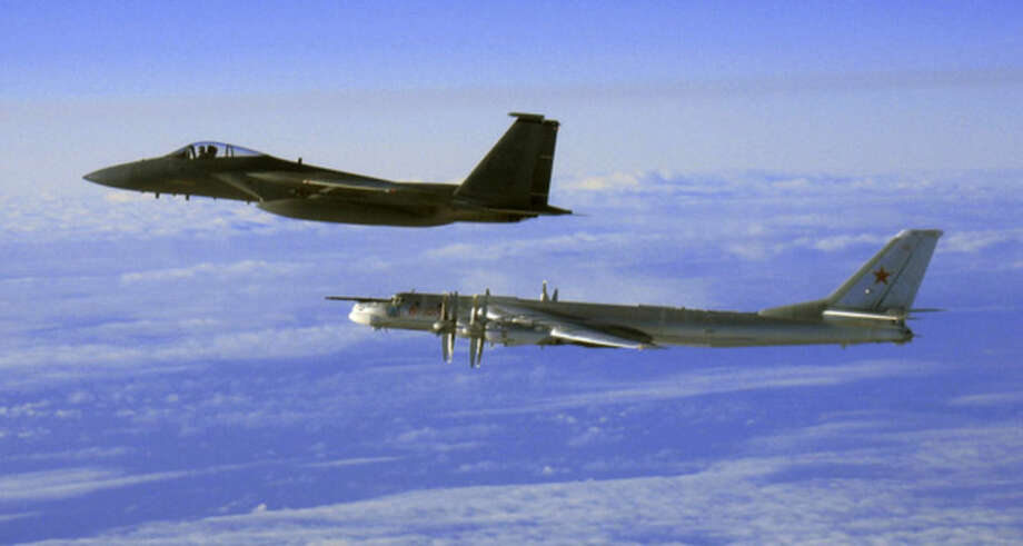 """FILE - This Thursday, Sept. 28, 2006 file photo provided by the U.S. Air Force shows an F-15C Eagle from the 12th Fighter Squadron at Elmendorf Air Force Base in Anchorage, Alaska, flying next to a Russian Tu-95 """"Bear"""" bomber, right, during a Russian exercise which brought the bomber near the west coast of Alaska. Russia's defense minister says the military will conduct regular long-range bomber patrols, ranging from the Arctic Ocean to the Caribbean and the Gulf of Mexico. (AP Photo/U.S. Air Force)"""