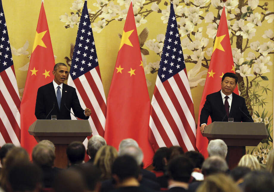 U.S. President Barack Obama, left, speaks next to Chinese President Xi Jinping during their joint press conference at the Great Hall of the People in Beijing Wednesday, Nov. 12, 2014. (AP Photo/Andy Wong)