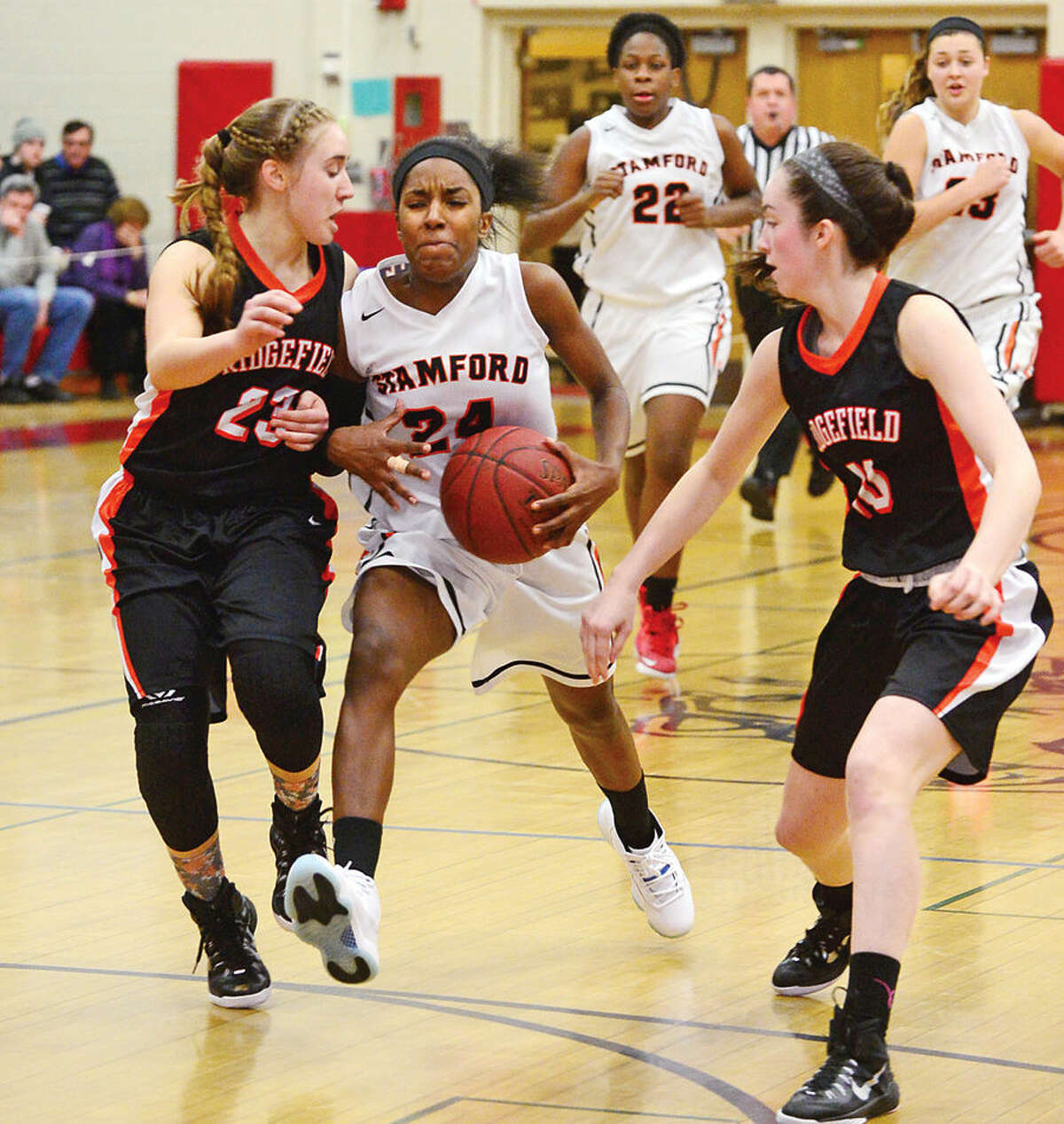 Stamford High School 's #24 Tiana England battles Ridgefield's #23 Jessica Camarda and #10 Megan O'Hara during the FCIAC Girls Basketball Quarterfinals Saturday at Fairfield Warde High School.