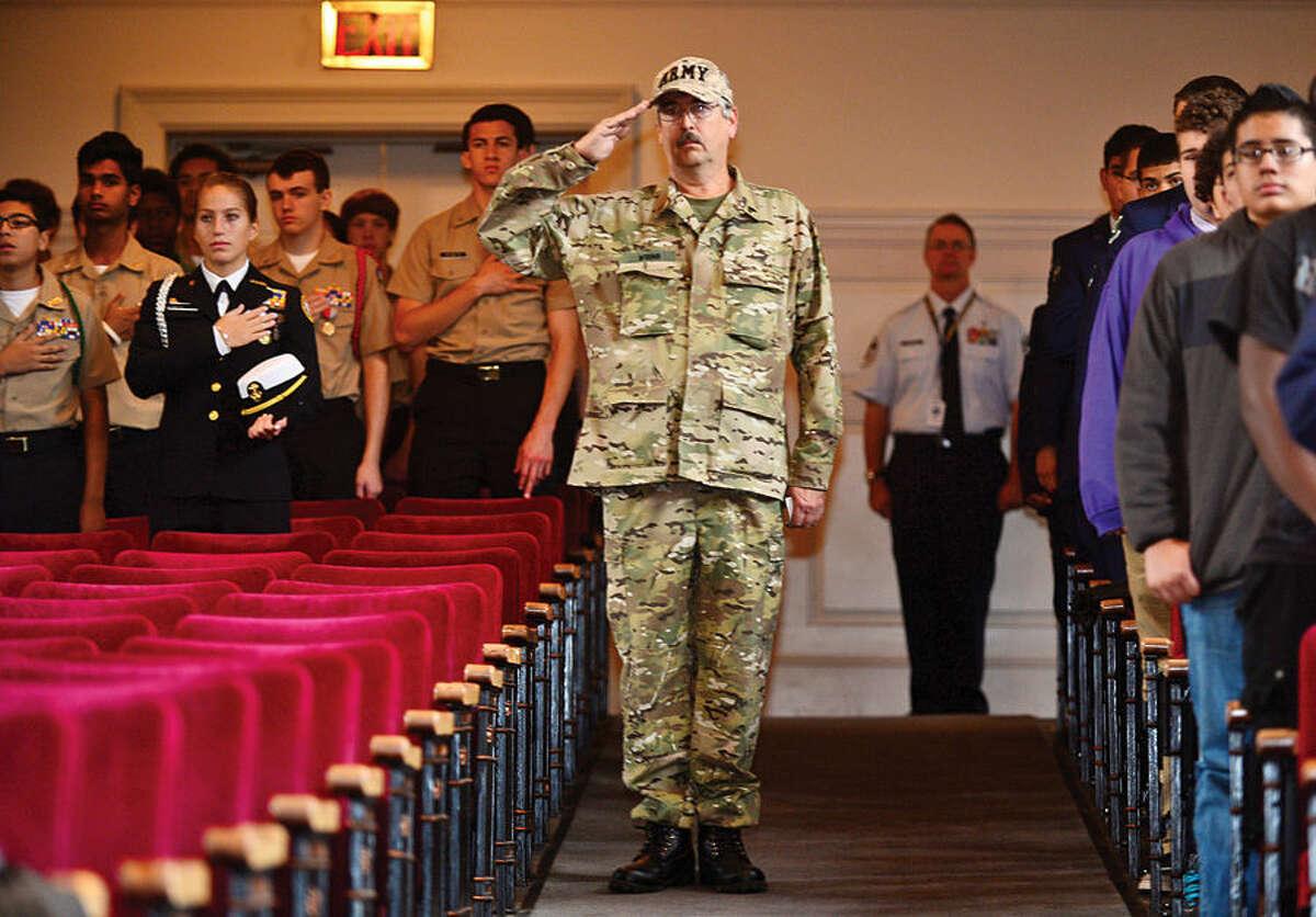 Hour photo / Erik Trautmann Army Veteran and parade marshal Jim Wrinn salutes the flag during the Norwalk Veteran's Day celebration at City Hall Tuesday morning.