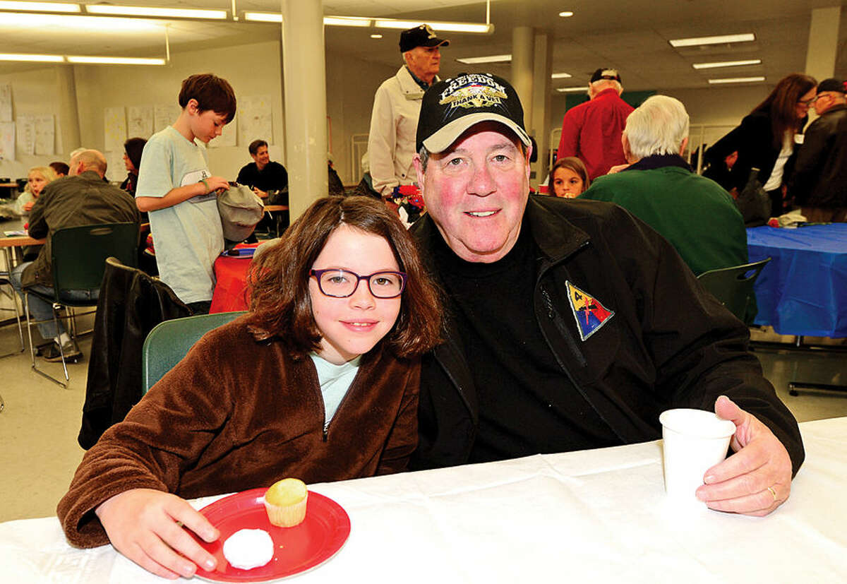 Hour photo / Erik Trautmann Cider Mill 3rd grader Sarah Bennett and her grandfather, army veteran Barry Seigerman, share a moment following a Veteran's Day ceremony at Cider Mill Elementary School in Wilton Tuesday.