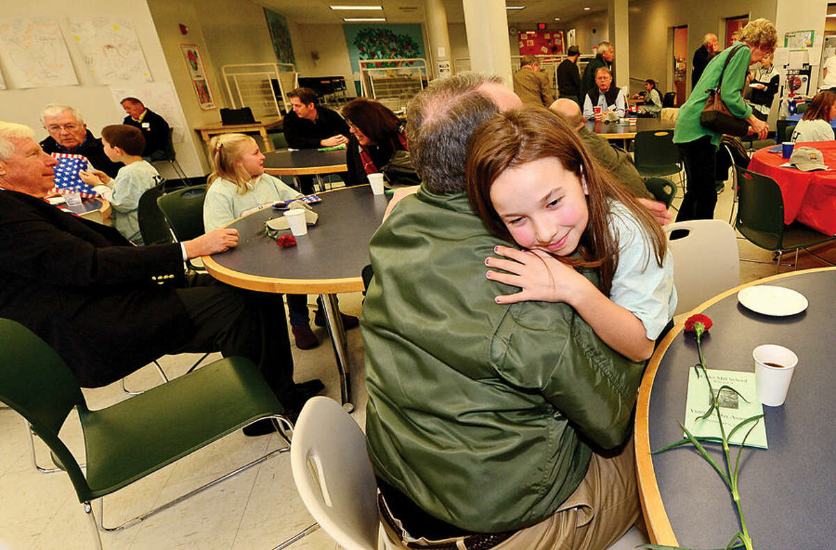 Hour photo / Erik Trautmann Marine Corps veteran Greg Sweeeney gets a hug from his grandaughter, 3rd grader Rylee Sweeney, following a Veteran's Day assembly at Cider Mill Elementary School in Wilton Tuesday.