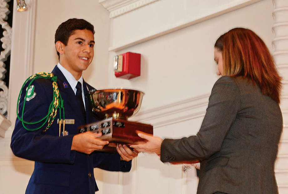 Hour photo / Erik Trautmann Norwalk High School Air Force ROTC cadet Camilo Builes accepts the Stew Leonard trophy for his school during Norwalk Veteran's Day celebration at City Hall Tuesday morning.