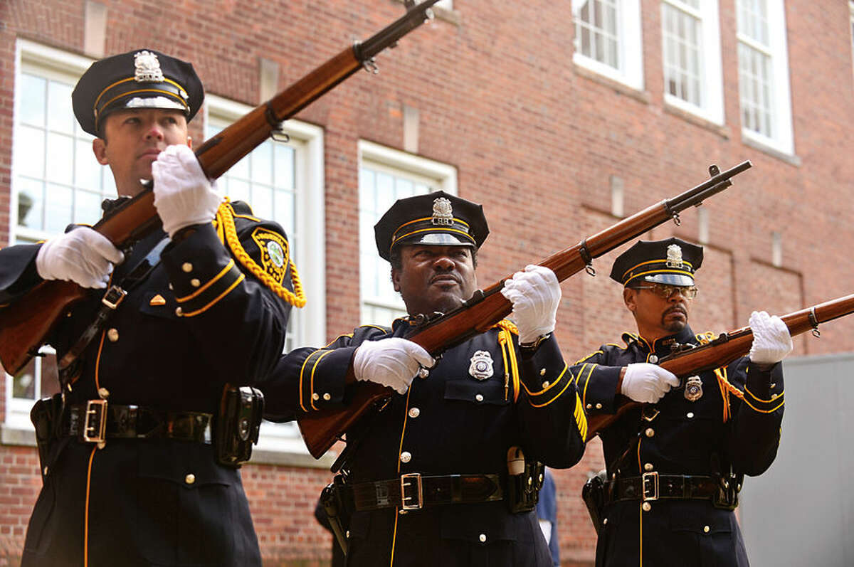 Hour photo / Erik Trautmann The Norwalk Police Department Honor Guard fire a volley in recognition of Norwalk Veteran's Day at City Hall Tuesday morning.