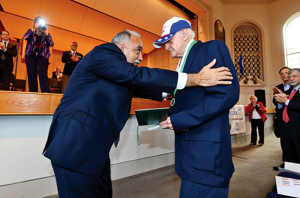 Hour photo / Erik Trautmann Norwalk Superintendent of Schools Manual Rivera presents WWll army veteran Michael James Hegodus with a honorary diploma during the Norwalk Veteran's Day celebration at City Hall Tuesday morning.