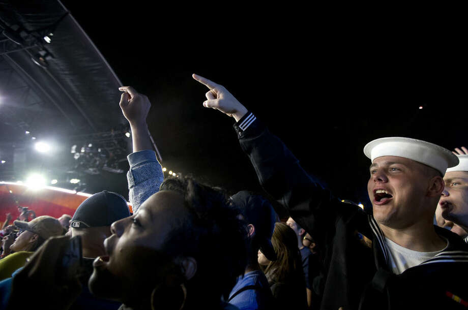 Jerrod Knight of the Navy Ceremonial Guard, right, cheers with the crowd on the National Mall in Washington, Tuesday, Nov. 11, 2014, during the Concert for Valor. The Veterans Day event is hosted by HBO, Starbucks and Chase and is free and open to the public. (AP Photo/Carolyn Kaster)