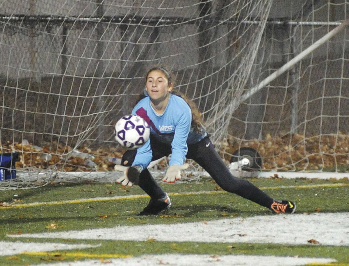 Hour photo/John Nash Weston goalkeeper Isabel Berch makes one of her eight saves during Tuesday's Class M girls soccer semifinal at Falcon Field in Meriden. The Trojans knocked off Suffield with a 3-2 (8-7 PKs) win to advance to the state championship game.