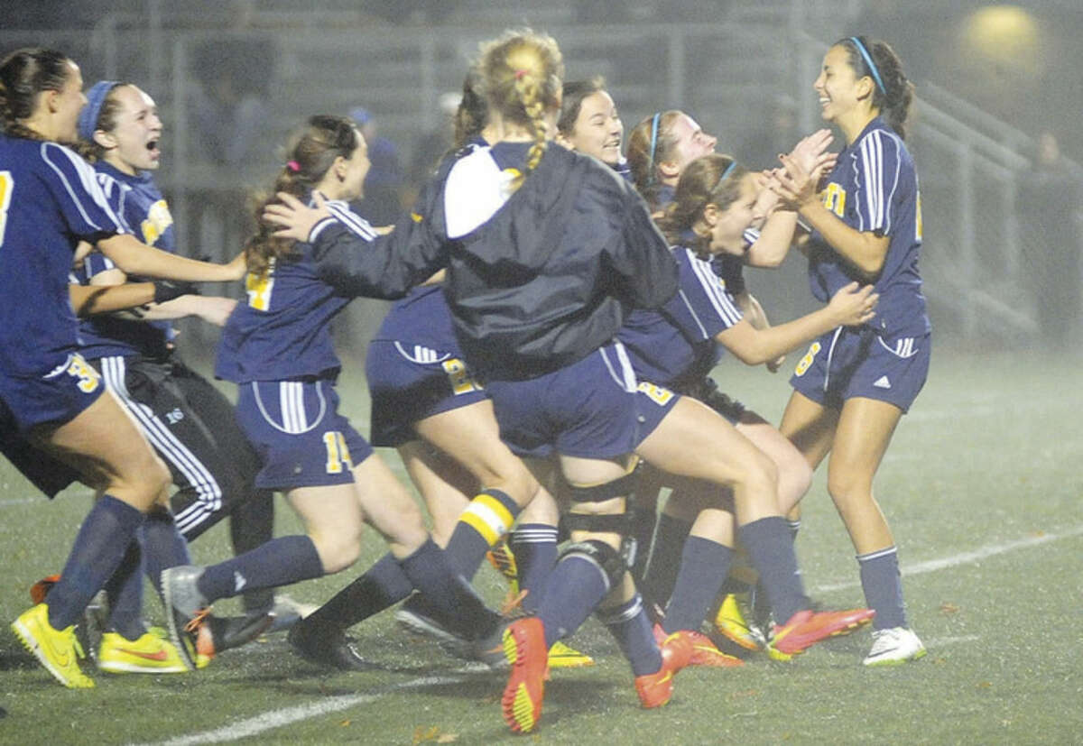 Hour photo/John Nash Weston's Hannah Campos, far right, is mobbed by teammates after her penalty kick capped off the Trojans' 3-2 (8-7 PK) victory over Suffield on Tuesday night at Falcon Field in Meriden.
