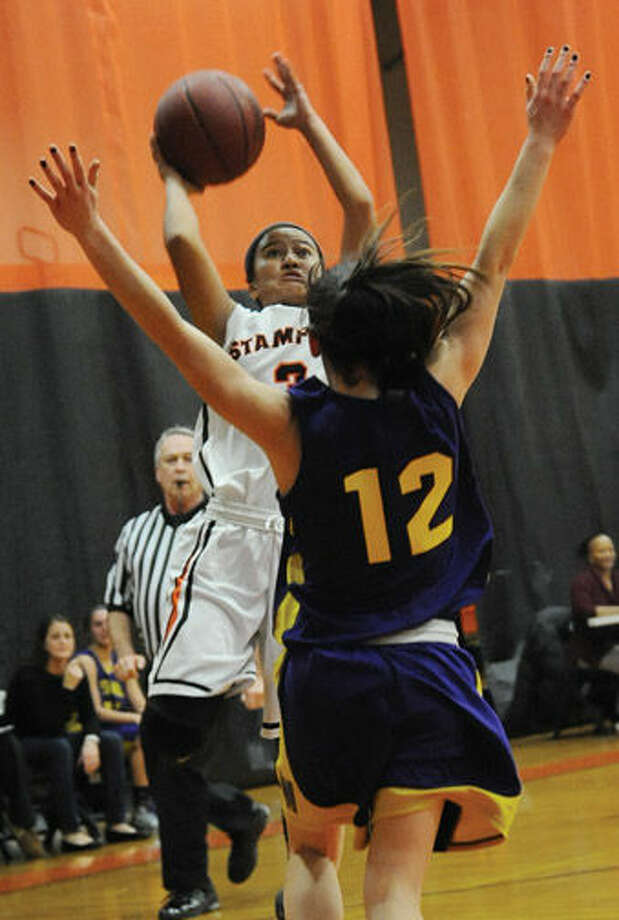 Stamford's Camille Martinez takes a shot over Westhill's Olivia Wise.