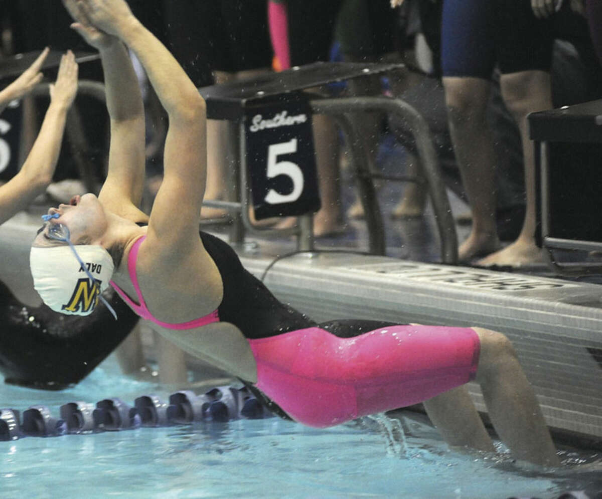 Hour photo/John Nash Kiersten Daly of Weston kicks off the Class M state championship swim meet in the opening leg of the 400 medley relay at the Southern Connecticut State University pool on Tuesday night. Weston won the event and the meet, its second straight state title.
