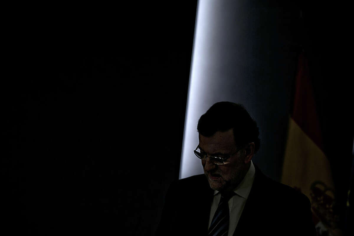 Spain's Prime Minister Mariano Rajoy looks down during a press conference at the Moncloa Palace in Madrid, Spain, Wednesday, Nov. 12, 2014. Prime Minister Rajoy speaks to evaluate the Catalonian non-binding vote on secession from Spain. Catalonia's regional President Artur Mas opted for an unofficial consultation after parliament, where Rajoy's Popular Party has a majority, rejected his call for a referendum and Spain's judiciary concurred. (AP Photo/Daniel Ochoa de Olza)