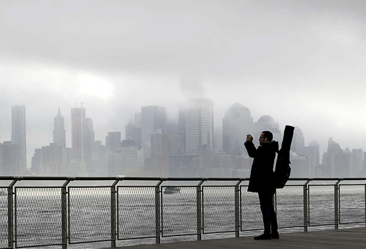 Richard Espinal, of New York City, pauses during his walk to work as a music instructor to photograph the fog blanketing New York City, Wednesday, Nov. 12, 2014, from the Hudson River front in Hoboken, N.J. The National Weather Service said the fog reduced visibility to a quarter mile or less. Motorists were advised to slow down. (AP Photo/Julio Cortez)