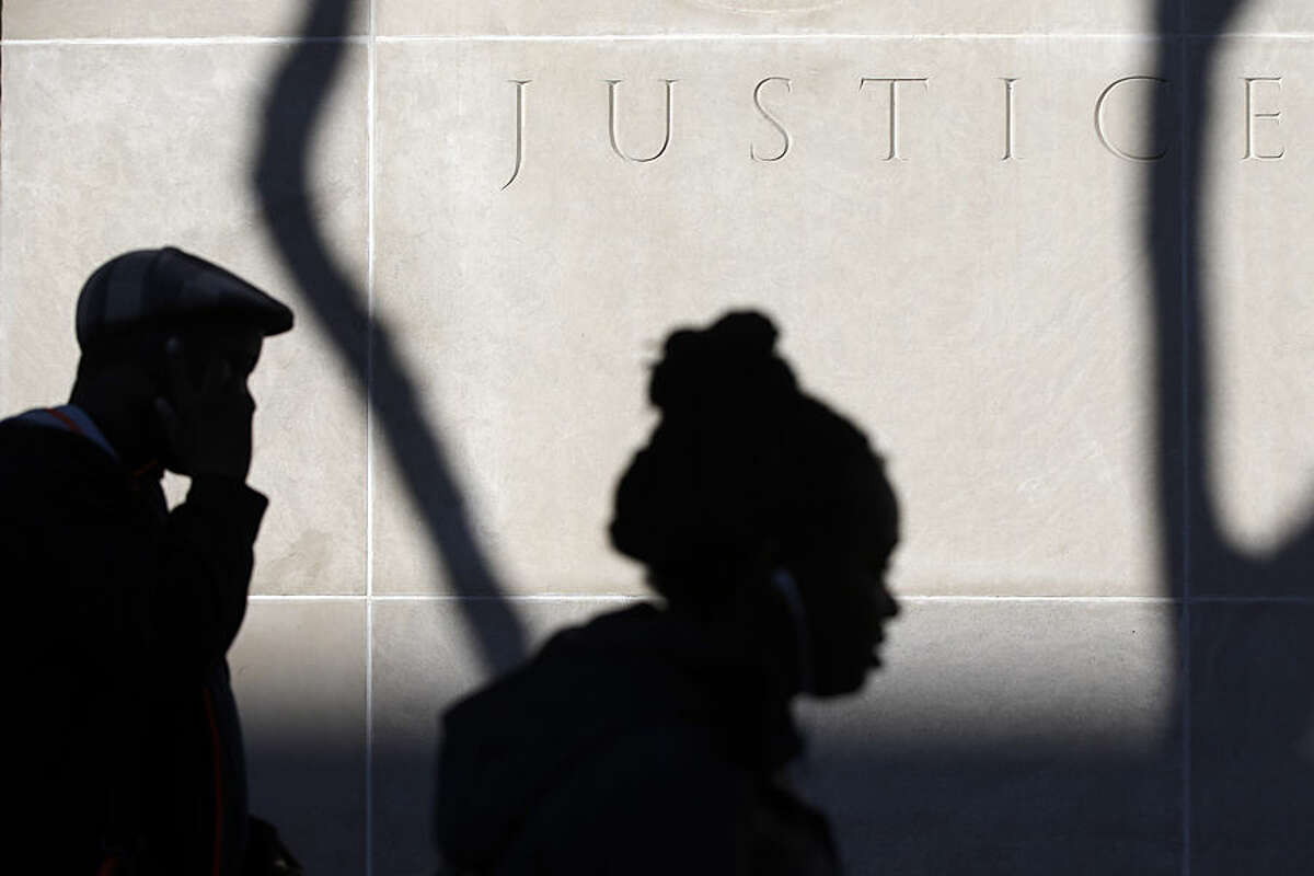 Pedestrians walk past a shadow cast by a tree stripped of its leaves on an autumn afternoon, Wednesday, Nov. 12, 2014, outside of the U.S. Courthouse in Philadelphia. (AP Photo/Matt Rourke)