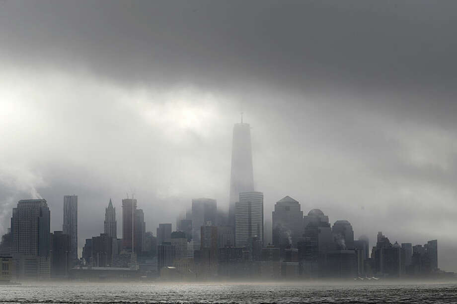 Heavy fog blankets lower Manhattan in New York, including One World Trade Center, center, in this view across the Hudson River from Hoboken, N.J., Wednesday, Nov. 12, 2014. The National Weather Service said the fog reduced visibility to a quarter mile or less. (AP Photo/Julio Cortez)