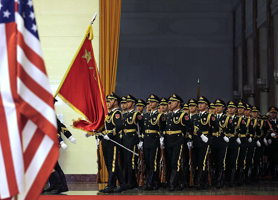 Chinese guard of honor march into a hall during a welcome ceremony for visiting U.S. President Barack Obama at the Great Hall of the People in Beijing, China Wednesday, Nov. 12, 2014. (AP Photo/Andy Wong)