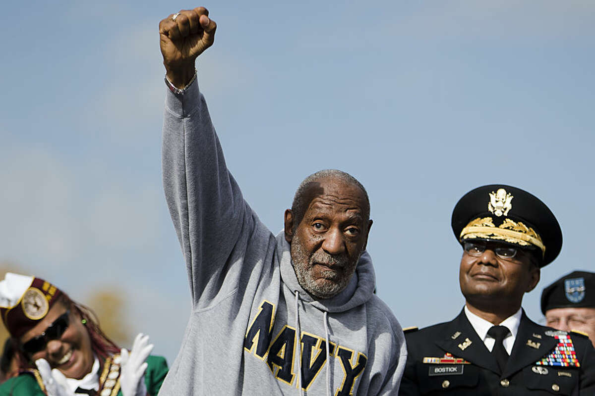 Entertainer and Navy veteran Bill Cosby, center, seated by Lt. Gen.Thomas Bostick, right, gestures as he listens to remarks during a Veterans Day ceremony, Tuesday, Nov. 11, 2014, at the The All Wars Memorial to Colored Soldiers and Sailors in Philadelphia. Cosby told the crowd during a 20-minute address that