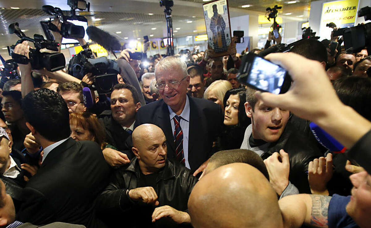 Serbian ultranationalist leader Vojislav Seselj, center leaves after landing at Belgrade airport from The Hague, Netherlands, where he is on trial at a U.N. war crimes tribunal, Wednesday, Nov. 12, 2014. Seselj, who spent more than 11 years in detention for his role in the Balkan wars of the 1990's, was granted a temporary release because of his deteriorating health. (AP Photo/Darko Vojinovic).