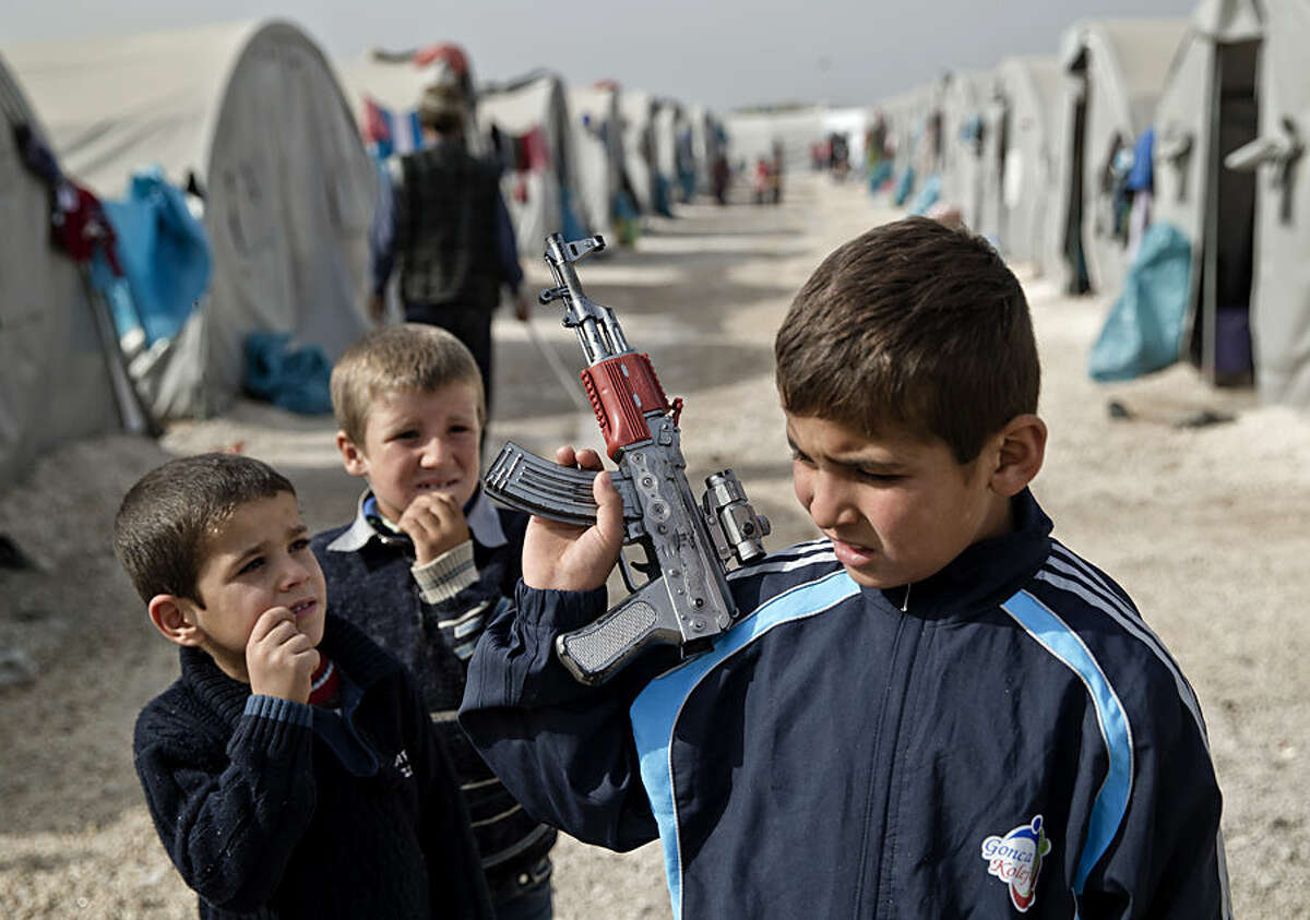 A Syrian Kurdish refugee boy from the Kobani area, holds a toy weapon at a camp in Suruc, on the Turkey-Syria border Thursday, Nov. 13, 2014. Kobani, also known as Ayn Arab, and its surrounding areas, has been under assault by extremists of the Islamic State group since mid-September and is being defended by Kurdish fighters. (AP Photo/Vadim Ghirda)