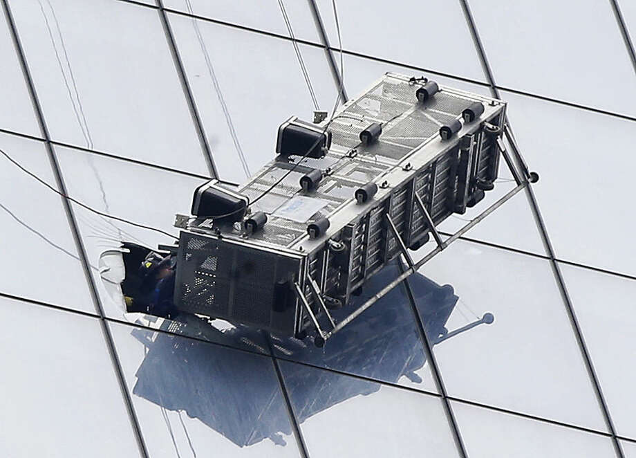 A firefighter reaches through a cut-out window into a dangling work basket to rescue two window washers from outside 1 World Trade Center in New York, Wednesday, Nov. 12, 2014. The two window washers were trapped for more than an hour. (AP Photo/Kathy Willens)