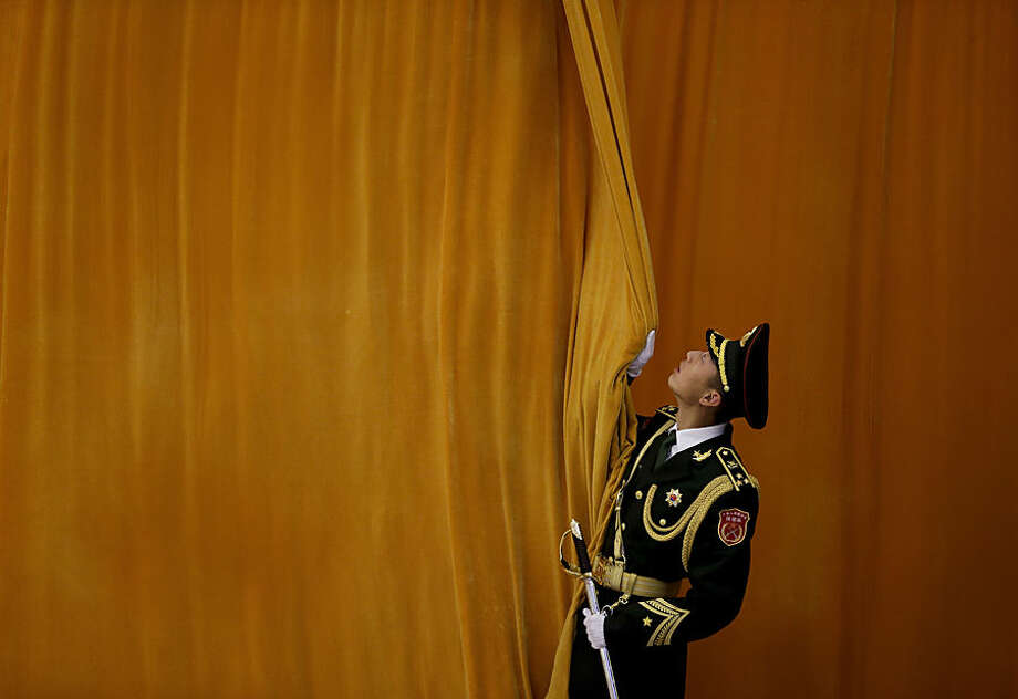 A Chinese People's Liberation Army soldier closes a curtain as preparations for a welcome ceremony held by Chinese President Xi Jinping for visiting Mexican President Enrique Pena Nieto at the Great Hall of the People in Beijing Thursday, Nov. 13, 2014. (AP Photo/Andy Wong)