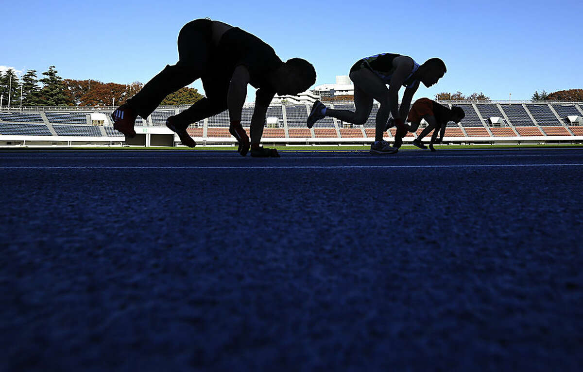 Competitors run on their arms and legs on a race course in a preliminary race during the Guinness World Record the 100-meter running on all fours at Komazawa Olympic Park Stadium in Tokyo Thursday, Nov. 13, 2014 in celebration of Guinness World Records Day. The 18-year-old Japanese Katsumi Tamakoshi set new record of 15.86 seconds Thursday. (AP Photo/Eugene Hoshiko)