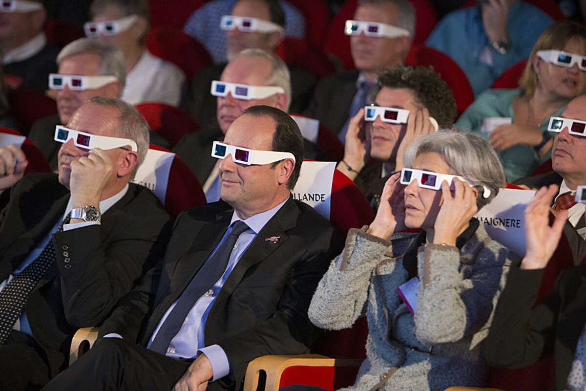 French National Centre for Space Studies (CNES) president Jean-Yves Le Gall, left, French President Francois Hollande, center, and former French minister and astronaut Claudie Haignere, right, wear 3D glasses as they visit the Cite des Sciences at La Villette during a broadcast of the Rosetta mission as it orbits around comet 67/P Churyumov-Gersimenko in Paris, Wednesday, Nov. 12, 2014. Hundreds of millions of miles from Earth, a European spacecraft made history Wednesday by successfully landing on the icy, dusty surface of a speeding comet - an audacious first designed to answer big questions about the universe. (AP Photo/Jacques Brinon, Pool)