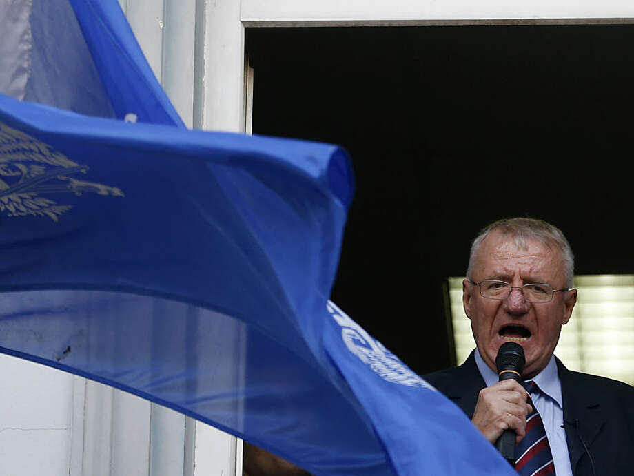 Serbian ultranationalist leader Vojislav Seselj speaks to supporters from the party headquarters after arriving in Belgrade from The Hague, Netherlands Wednesday, Nov. 12, 2014. Serbian far-right leader Vojislav Seselj, accused of recruiting notorious paramilitary forces during the bloody 1990s Balkan wars, arrived home to a boisterous welcome Wednesday after U.N. war crimes judges approved his provisional release due to ill health. (AP Photo/Darko Vojinovic).